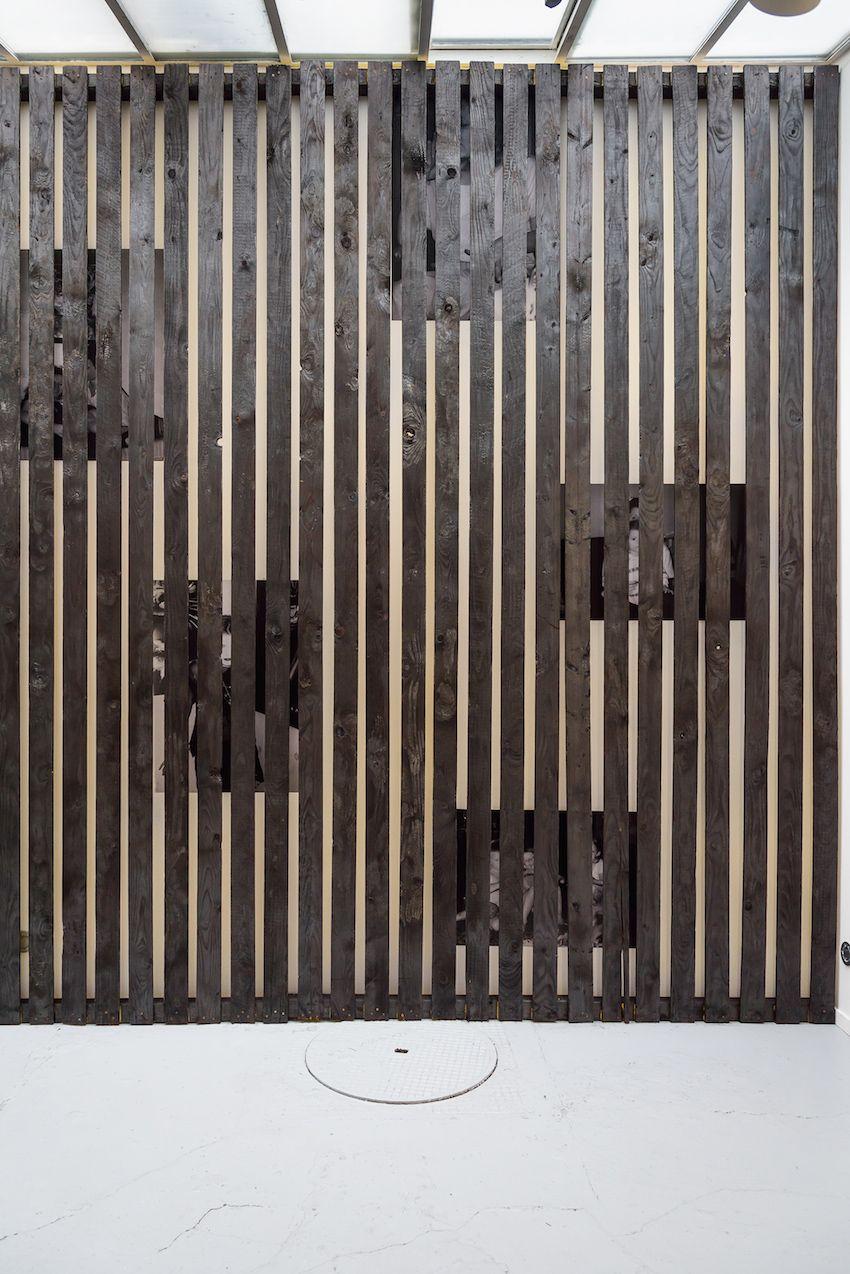 alicia-zaton-za-2014-2015-installation-en-brois-brule-a-la-dimension-du-mur-de-la-galerie-poster-d-archives-personnelles-colle-au-mur-derrieres-des-lattes-de-bois-590x370cm-0a309b0b8589d2ca34cc5d822e988030
